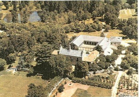 """Vista aérea de La Fresneda. En ésta es posible ver la Casa del Rey con su cubierta a dos aguas escalonada y la  Casa de los Monjes, en forma de """"U"""" y con el patio de columnas toscanas. Asimismo es posible ver uno de los estanques que forman parte de la propiedad."""