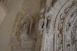 Detalle de las decoraciones de cardo y figuras de la portada gótica de la Iglesia.
